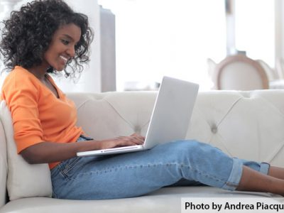 Girl sitting on couch working at computer